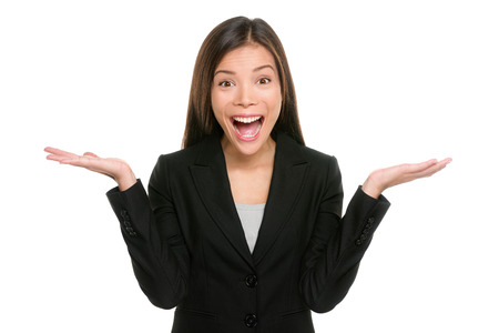 Surprised businesswoman with hands up amazed or shocked by unexpected news holding open palms up for copy space and showing happy expression. Asian mixed race young adult woman on white background. Stockfoto