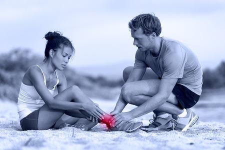 Esguince en el tobillo - entrenador de ayudar a corredor en el dolor. Atleta de la mujer que tiene accidente en funcionamiento durante el maratón, con esguince dolorosos en las piernas siendo ayudado por el entrenador personal o médico. Dos adultos activos en la playa.