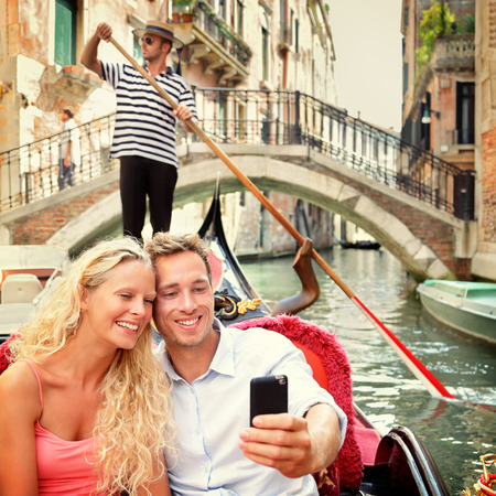 venice: Selfie couple in gondola on Venice travel vacation. Beautiful lovers on a romantic boat ride across the Venetian canals taking self-portrait pictures with smartphone app during their summer holidays.