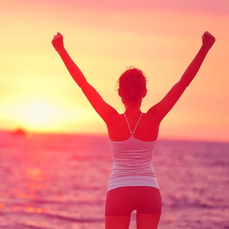 Realização da vida - a mulher feliz arma-se no sucesso. Vista traseira da silhueta feminina, orgulhosa de alcançar seus braços de objetivo de saúde levantou olhando para o oceano e o pôr do sol. Conceito de objetivo ganhar felicidade.