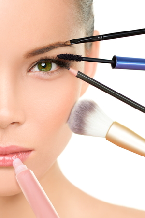 makeover: Makeup beauty transformation concept face makeover - Asian woman with many brushes against one side of the face putting mascara, blush and lip gloss Stock Photo