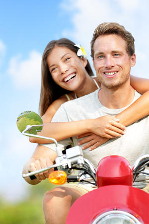 Scooter driving Happy young couple in love. Multiracial couple having fun in the free outdoor. Smiling Caucasian man and Asian woman. photo