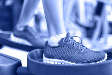 Cardio exercise - Elliptical workout machine in gym. Closeup of female feet using equipment at the fitness center for working out the legs. Sports and recreation concept in Blue monochrome filter. Stock Photo