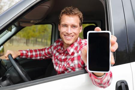 manejando: Smartphone hombre que conducía el auto que muestra la aplicación en pantalla sonriendo feliz. Conductor masculino que usa aplicaciones 4g muestran touchscreen vacío en blanco sentado en asiento del conductor. Centrarse en el modelo y en la pantalla para copiar el espacio.