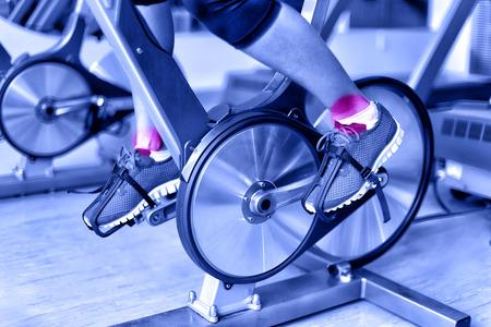 スポーツの傷害 - スピニング バイク ジムでのトレーニング中に足首の痛み。女性アスリートの足自転車マシンを使用して青の単色フィルターのフィ