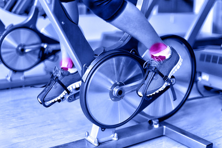 Sports injury - ankle pain during training on spinning bike at gym. Closeup of female athletes legs using bicycle machine at fitness center in blue monochromatic filter.