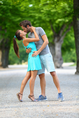 romantic kiss: First kiss - Young couple of lovers in love passionately kissing standing on path in summer park. Full body portrait of Caucasian male and Asian female in blue sundress loving and hugging each other.