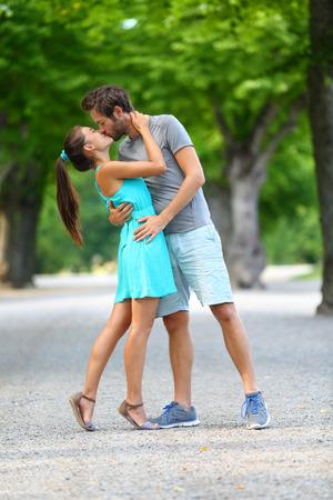 besos apasionados: Primer beso - Joven pareja de amantes en el amor apasionadamente bes�ndose de pie en el camino en el parque de verano. Retrato de cuerpo entero de var�n de raza blanca y asi�tica femenina en vestido de verano azul amar y abraz�ndose unos a otros. Foto de archivo