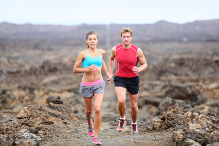 Active sport people runners on rocky trail running path outdoors training for marathon or triathlon. Fit young fitness model man and asian woman training together outside on Big Island, Hawaii, USA.