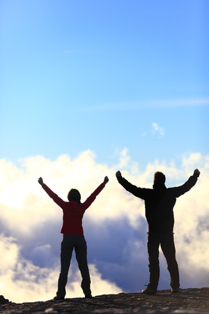 woman arms up: Happy winners reaching life goal - success people at summit. Business achievement concept. Two person couple together arms up in the air of happiness with accomplishment in the clouds at sunset. Stock Photo