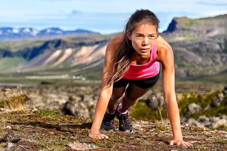 Fitness push-ups vrouw doet push-ups buiten in de natuur achtergrond. Gericht vrouwelijke atleet toont doorzettingsvermogen en uithoudingsvermogen te oefenen spieren tijdens lichaamskern CrossFit workout in de zomer landschap. Stockfoto