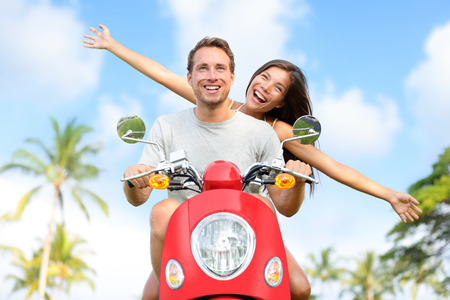 drivers: Happy free freedom couple driving scooter excited on summer holidays vacation. Young multiethnic couple in love, Asian woman, Caucasian man