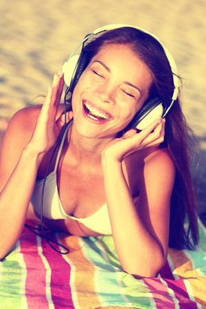 toallas: Mujer escuchando m�sica con auriculares en la playa. Muchacha asi�tica joven relajarse durante las vacaciones de verano que se acuesta con la toalla en la arena de oro que disfruta de sus vacaciones cantando feliz. Foto de archivo