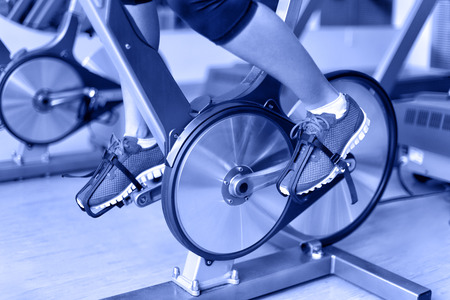 Exercise bike with spinning wheels. Woman excising biking in fitness center. closeup of pedals. Professional fitness center equipment. Stock Photo