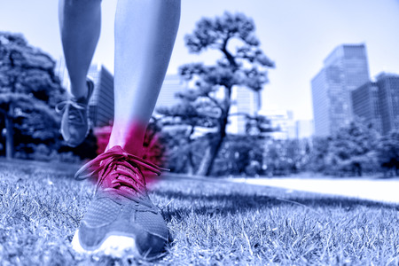 Blessures sportives - coureur pieds avec des douleurs à la cheville. Gros plan de chaussures de course d'atterrissage sur l'herbe douce avec cercle rouge montrant les articulations et les ligaments blesser causés par un traumatisme de fitness. Banque d'images
