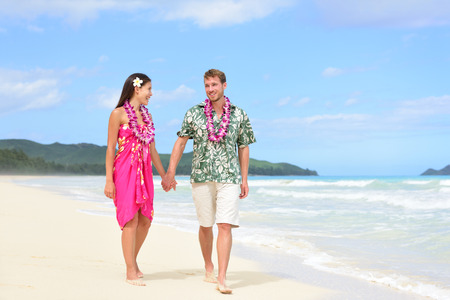hawaiian lei: Happy couple on Hawaii vacation walking on beach with Hawaiian leis and Aloha clothing. Caucasian man wearing typical Hawaiian shirt and Asian woman girlfriend in pink sarong fabric sundress.