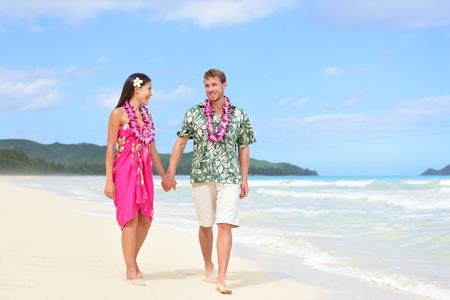 hawaiana: Pareja feliz en Hawai de vacaciones a pie de playa con leis hawaianos y ropa de Aloha. Hombre de raza caucásica llevaba camisa hawaiana típica y mujer novia asiática en rosa vestido de verano de tela sarong.