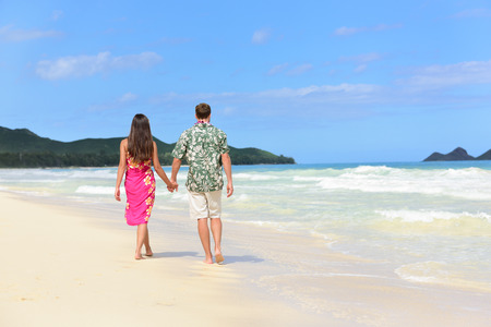 Hawaii honeymoon couple of newlyweds walking on tropical beach in Hawaiian apparel, pink sarong dress and green Aloha shirt for Polynesian cultural tradition. Young people holding hands happy in love. photo