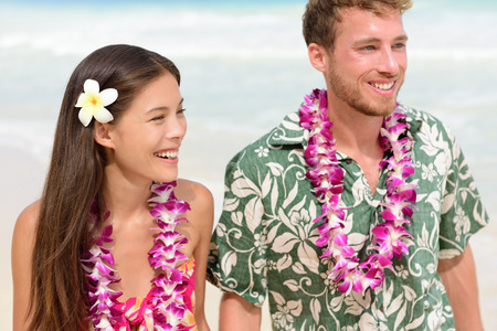 leis: Happy Hawaii beach couple in Aloha Hawaiian shirt. Portrait of Asian woman and Caucasian man on beach walking with flower leis and typical attire for their wedding or honeymoon.