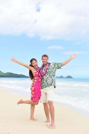 leis: Felice Hawaii vacanza coppia divertirsi in vacanza in spiaggia alle Hawaii in piedi su perfetto sabbia bianca con le braccia in gioia e felicit�. La gente pronta per le vacanze estive che mostra la libert� e il successo.