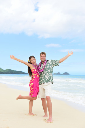 leis: Happy Hawaii vacation couple having fun on beach holidays in Hawaii standing on perfect white sand with arms up in joy and happiness. People ready for summer vacations showing freedom and success.