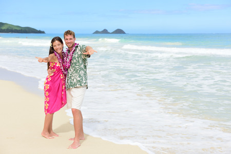 leis: Portrait of couple of tourists happy standing on Hawaiian beach at their Hawaii vacation. Asian woman and Caucasian man wearing flower lei garland and Aloha clothing showing Shaka hand sign on travel.