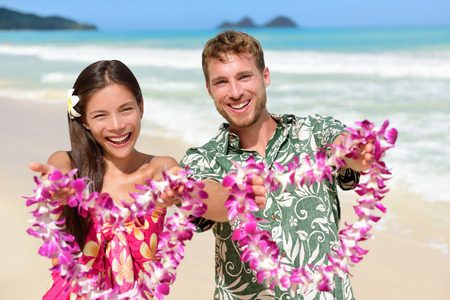 leis: Welcome to Hawaii - Hawaiian people showing leis flower necklaces as a welcoming gesture for tourism. Travel holidays concept. Asian woman and Caucasian man on white sand beach in Aloha clothing. Stock Photo