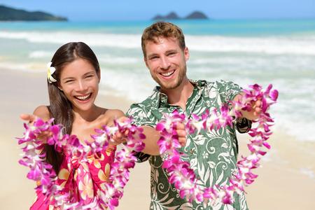 Welkom op Hawaii - Hawaiian mensen laten zien leis bloemenkettingen als een gastvrije gebaar voor het toerisme. Reizen vakantie concept. Aziatische vrouw en blanke man op wit zandstrand in Aloha kleding. Stockfoto