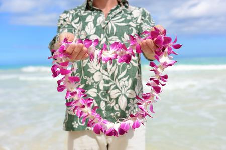 Tradizione delle Hawaii - regala una fioriera hawaiana. Ritratto di una persona di sesso maschile in possesso di una ghirlanda di fiori come la cultura hawaiana accogliente gesto per i turisti che viaggiano verso le isole del Pacifico.