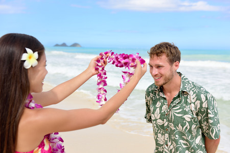 welcome people: Hawaii woman giving lei garland of pink orchids welcoming tourist on Hawaiian beach. Portrait of a Polynesian culture tradition of giving a flower necklace to a guest as a welcome gesture. Stock Photo