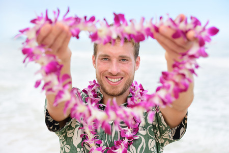 leis: Hawaii Caucasian man with welcome Hawaiian lei. Male tourist portrait holding flower necklace giving it to the camera as a welcoming gesture for tourism in Hawaii. Travel vacation concept.