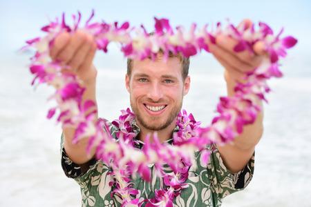 leis: Hawaii uomo caucasico con Hawaiian lei di benvenuto. Ritratto maschile turista collana di fiori di partecipazione dando alla macchina fotografica come un gesto di benvenuto per il turismo nelle Hawaii. Viaggiare concetto di vacanza. Archivio Fotografico