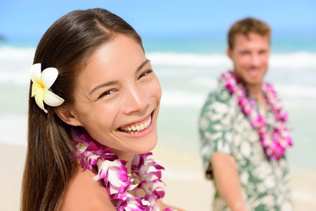 lei: Happy Hawaii couple in Hawaiian lei, flower head and Aloha shirt. Portrait of a smiling Asian multiracial woman with Caucasian boyfriend on beach, multiethnic couple on summer travel vacations.