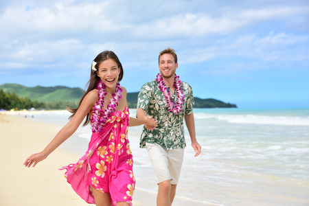 Happy couple having fun running on Hawaii beach vacations in Hawaiian clothing wearing Aloha shirt and pink sarong sun dress and flower leis for traditional wedding or honeymoon concept.