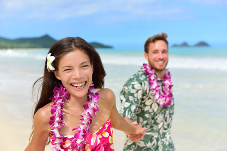 leis: Happy Hawaii beach holiday couple in Aloha shirt and dress and wearing Hawaiian flower leis as a Polynesian culture tradition for welcoming tourists or for a wedding or honeymoon vacation. Stock Photo