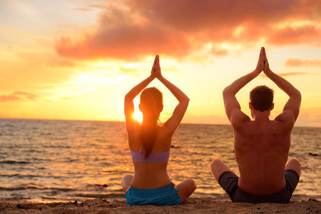 wellness: Yoga couple relaxing doing meditation on beach. Silhouettes of man and woman people practicing yoga pose sitting at a beach in the lotus position with their hands raised against a colorful sunset sky.