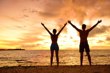 victory: Freedom people living a free, happy, carefree life at beach. Silhouettes of a couple at sunset arms raised up showing happiness and a healthy lifestyle against a colorful sky of clouds background.