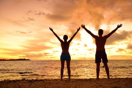 Liberté des gens vivant une vie libre, heureuse et sans soucis à la plage. Silhouettes d'un couple au coucher du soleil, bras levés, montrant le bonheur et un mode de vie sain avec un ciel coloré de fond de nuages.