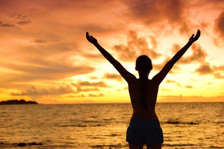 manos levantadas al cielo: Libertad silueta de la mujer que vive un estilo de vida saludable vida despreocupada y libre felices. Retrato de la parte posterior de un adulto femenino irreconocible en vacaciones en la playa en la puesta del sol con los brazos levantados hacia el cielo. Foto de archivo