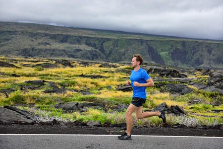 Atleet mannelijke loper die op bergweg. Running man joggen snelle training cardio voor marathon op het platteland pad in de natuur landschap, vulkaan achtergrond. Jonge Kaukasische volwassen in zijn jaren '20. Stockfoto