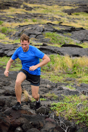 ultra: Active man trail running on volcanic rocks in mountain background. Male athlete racing doing an ultra marathon through rugged landscape in Hawaii, USA. Stock Photo