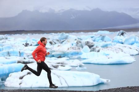 hombre deportista: Corredor. Sprint corredor de pista en el sprint rápido en el hermoso paisaje de la naturaleza. País masculino apto atleta velocista través funcionamiento por témpanos en Jokulsarlon lago glaciar en Islandia.