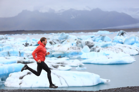 Running man. Sprinting trail runner in fast sprint in beautiful nature landscape. Fit male athlete sprinter cross country running by icebergs in Jokulsarlon glacial lake in Iceland.