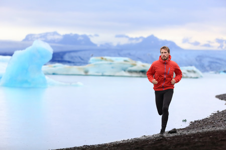 winter sports: Running man. Trail runner training for marathon run in beautiful nature landscape. Fit male athlete jogging and cross country running by icebergs in Jokulsarlon glacial lake in Iceland.