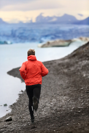 jogging: Runner man trail running training for run in beautiful nature landscape. Fit male athlete jogging and cross country running by icebergs in Jokulsarlon glacial lake in Iceland.