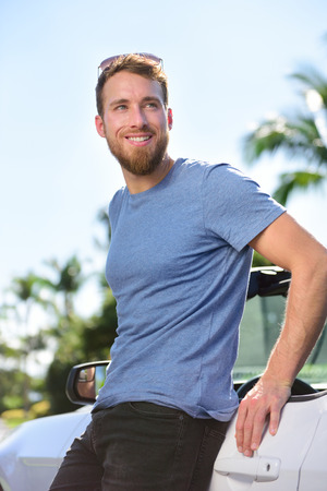 young adult man: New car owner - happy young urban and trendy man portrait standing next to a grey convertible. Smiling Caucasian bearded male adult driving his new purchase or rental. Summer road trip concept. Stock Photo