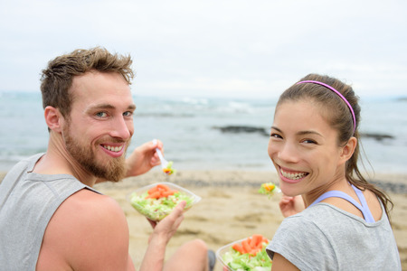 Vegan friends eating vegetarian salad meal during lunch break on beach happy looking at camera. Multiethnic group of young people, Caucasian man, Asian chinese mixed race woman in their 20s. Stock Photo