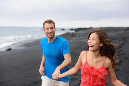 Happy couple laughing together walking on beach holidays. Vacation concept of two adult people holding hands on secluded black sand beach on volcanic island enjoying their getaway holiday.