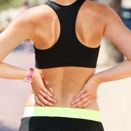 low back: Sports injury - Lower back pain woman holding body touching painful waist muscles showing smartwatch on wrist.. Stock Photo