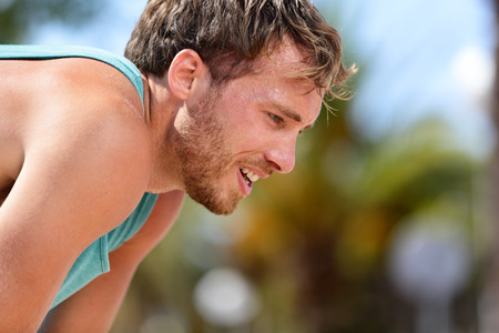 runners: Tired exhausted man runner sweating after cardio workout. Running male adult taking a break and breaking a sweat after a run under the sun. Fitness athlete breathing heavily from heat exhaustion. Stock Photo